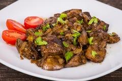 Куриные печени в сметанообразном соусе с луком на белой плите Стоковые Изображения
