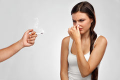 курить Красивая женщина держа нос, пахнуть запах сигареты Стоковое Изображение RF