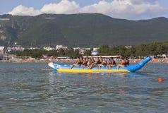 Курортный город деятельностям при пляжа Gelendzhik Люди едут на раздувной шлюпке банана в заливе Gelendzhik Стоковое Фото