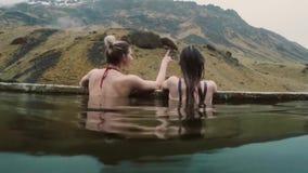 Курорт горячего источника геотермический в Исландии Путешествуя женщина 2 ослабляя в горячем бассейне с красивым ландшафтом на го видеоматериал