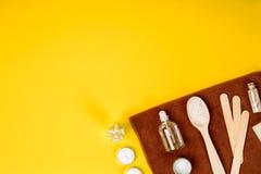 Курорт или установка здоровья в белых цветах Бутылки с необходимой ароматностью смазывают, полотенца, соль моря на желтой предпос Стоковые Фото