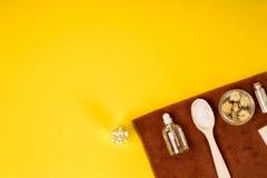 Курорт или установка здоровья в белых цветах Бутылки с необходимой ароматностью смазывают, полотенца, соль моря на желтой предпос Стоковые Фотографии RF