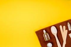 Курорт или установка здоровья в белых цветах Бутылки с необходимой ароматностью смазывают, полотенца, соль моря на желтой предпос Стоковое Фото
