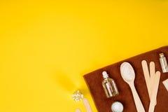 Курорт или установка здоровья в белых цветах Бутылки с необходимой ароматностью смазывают, полотенца, соль моря на желтой предпос Стоковое Изображение RF