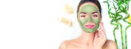 Курорт Молодая женщина прикладывая лицевую зеленую маску глины в салоне спа Косметики Skincare стоковое изображение rf
