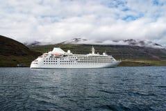Курсировать для удовольствия Туристическое судно в море на ландшафте горы в Sejdisfjordur, Исландии Океанский лайнер в море с стоковые фотографии rf