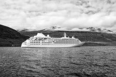 Курсировать для удовольствия Туристическое судно в море на ландшафте горы в Sejdisfjordur, Исландии Океанский лайнер в море с стоковое изображение