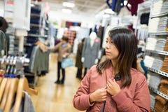 Куртка женщины пробуя в моле Стоковая Фотография