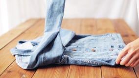 Куртка джинсовой ткани женщины складывая на деревянном столе дома сток-видео