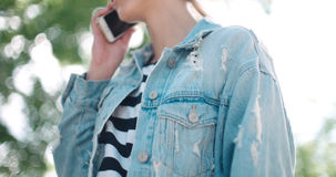 Куртка джинсовой ткани непознаваемой молодой женщины нося говоря на телефоне во время солнечного дня Стоковое Изображение