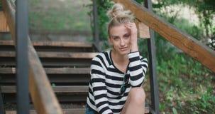 Куртка джинсовой ткани счастливой стильной девушки нося сидя на деревянных лестницах в парке города сток-видео