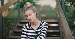 Куртка джинсовой ткани счастливой стильной девушки нося сидя на деревянных лестницах в парке города акции видеоматериалы