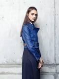 Куртка джинсовой ткани фотомодели нося и длинная черная юбка представляя в студии Стоковое Фото