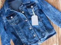 Куртка джинсов женская на деревянной предпосылке с ярлыком бирки Стоковое Фото