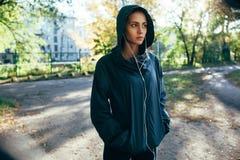Куртка клобука Sporty женщины нося и слушая музыка Стоковые Фото
