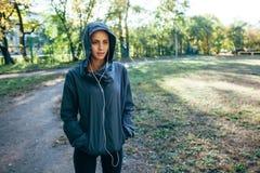 Куртка клобука Sporty женщины нося и слушая музыка Стоковое Изображение RF