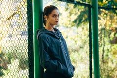 Куртка клобука Sporty женщины нося и слушая музыка Стоковое Изображение