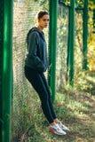 Куртка клобука Sporty женщины нося и слушая музыка Стоковая Фотография RF