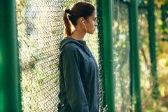 Куртка клобука Sporty женщины нося и слушая музыка Стоковые Фотографии RF