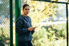 Куртка клобука Sporty женщины нося и слушая музыка Стоковые Изображения