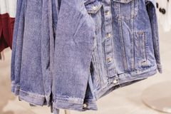 Куртки голубых джинсов в виде магазина на вешалке стоковое фото rf