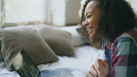 Курчавая Афро-американская молодая женщина имея видео- болтовню при друзья используя камеру компьтер-книжки пока лежащ на кровати видеоматериал