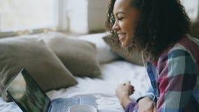 Курчавая Афро-американская молодая женщина имея видео- болтовню при друзья используя камеру компьтер-книжки пока лежащ на кровати Стоковые Изображения RF