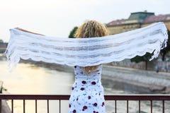 Курчавая белокурая девушка стоя на мосте и держа белое Sca Стоковое Изображение RF
