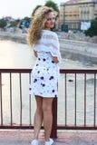 Курчавая белокурая девушка стоя на мосте и держа белое Sca Стоковое Изображение