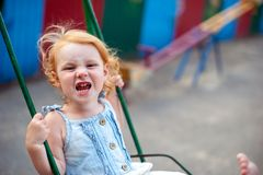 Курчавая девушка на кривой качания в парке Стоковое фото RF