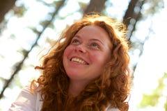 Курчавая девушка redhead смотря снаружи Стоковые Фотографии RF