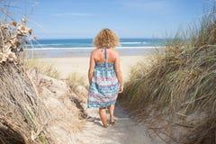 Курчавая женщина идя на взморье идет пристать задний взгляд к берегу Стоковое Изображение RF