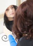 Курчавая женщина смотря зеркало парикмахером. В салоне парикмахерских услуг. Стоковая Фотография RF