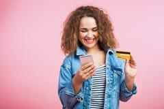 Курчавая красная женщина волос с мобильным телефоном и кредитной карточкой Стоковые Изображения