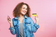 Курчавая красная женщина волос с мобильным телефоном и кредитной карточкой Стоковое Изображение