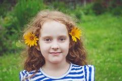 Курчавая маленькая девочка с маргариткой в ее волосах в парке лета Стоковые Изображения RF