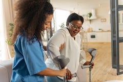 Курчавая молодая медсестра давая костыли достигшей возраста женщине после хирургии ноги стоковое фото rf