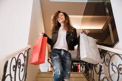 Курчавая молодая дама с хозяйственными сумками на лестнице Стоковое Изображение RF