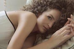 Курчавая молодая красивая девушка лежит на кровати в белом корсете и смотреть камеру Стоковое Изображение