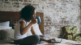 Курчавая привлекательная африканская девушка печатая на портативном компьютере для делить социальные средства массовой информации акции видеоматериалы