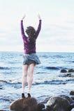 Курчавая с волосами женщина в платье и фуфайка на море приставают к берегу Стоковая Фотография