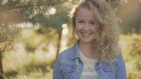 Курчавая усмехаясь белокурая девушка стоя под деревом в ярком свете Деревья на предпосылке, саде Женский портрет сток-видео