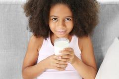 Курчавое Афро-американское питьевое молоко девушки Стоковое Изображение RF