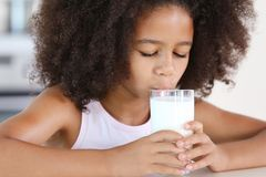 Курчавое Афро-американское питьевое молоко девушки Стоковые Фото