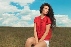 Курчавое брюнет сидя в полях с руками между ее ногами Стоковая Фотография RF