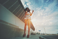 Курчавое привлекательное положение девушки и использование ее smartphome Стоковые Изображения
