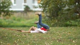 Курчавые бега школьника через парк с его собакой Мальчик спотыкается и непредвиденно падается вспомогательную видеоматериал