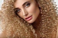 курчавые волосы Красивая женщина с естественными шикарными скручиваемостями волос Стоковые Фото