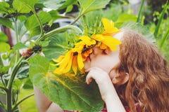Курчавый солнцецвет запаха девушки наслаждаясь природой в дне лета солнечном Стоковое Изображение RF