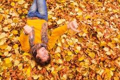 Курчавый человек в свитере и шарфе показывая tumbs вверх Стоковые Фотографии RF